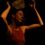 Femme avec cailloux sur la tête